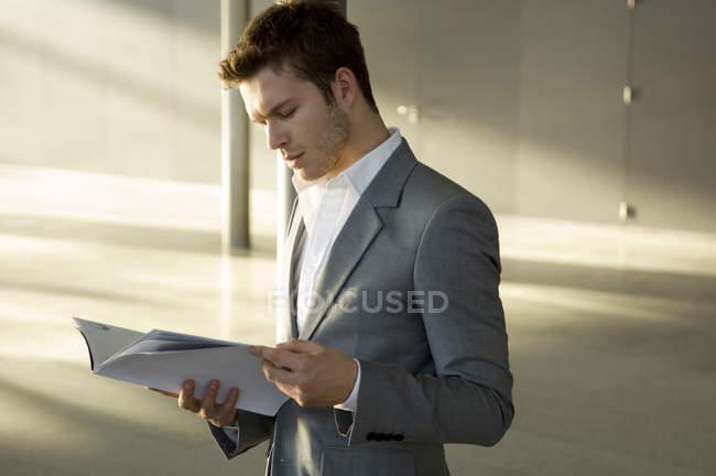 Revista de leitura elegante jovem empresário — Fotografia de Stock