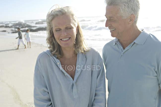 Sorridente coppia matura in piedi sulla spiaggia — Foto stock