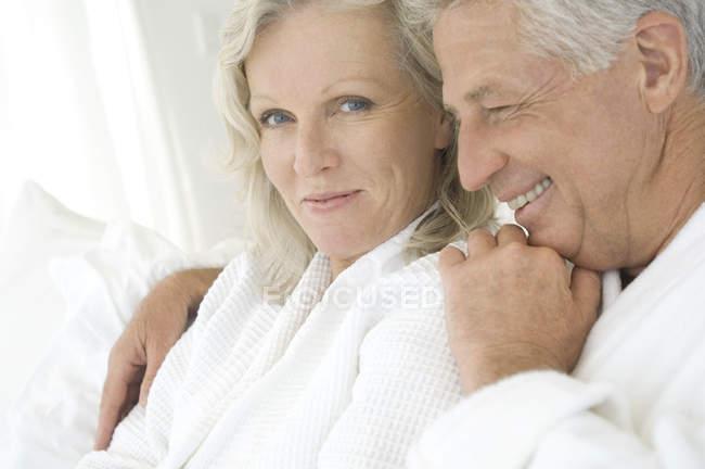 Портрет улыбающейся обнимающей пары в халатах — стоковое фото