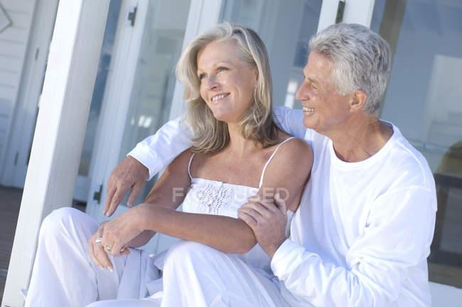 Reifes Paar, das auf der Terrasse sitzt und lächelt — Stockfoto