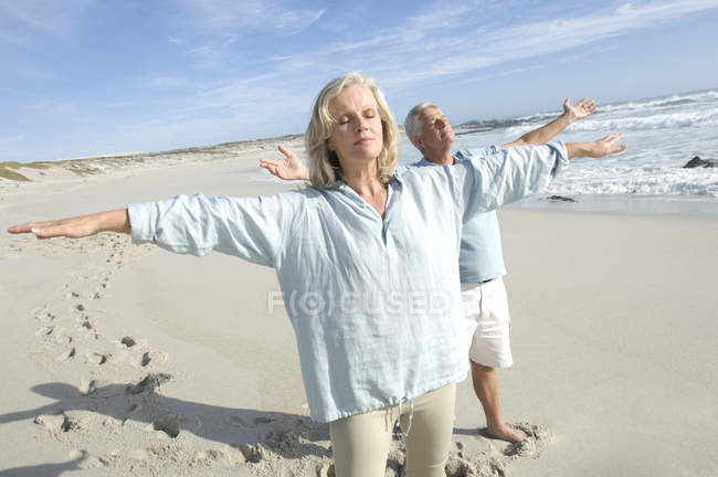 Couple with arms outstretched and eyes closed relaxing on beach — Stock Photo
