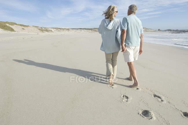Vista trasera de pareja adulta caminando en la playa cogidos de la mano - foto de stock