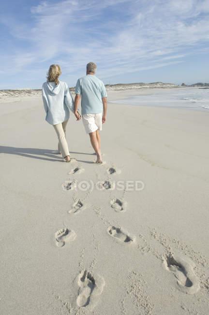 Rückansicht eines reifen Paares, das Händchen haltend am Strand spaziert — Stockfoto
