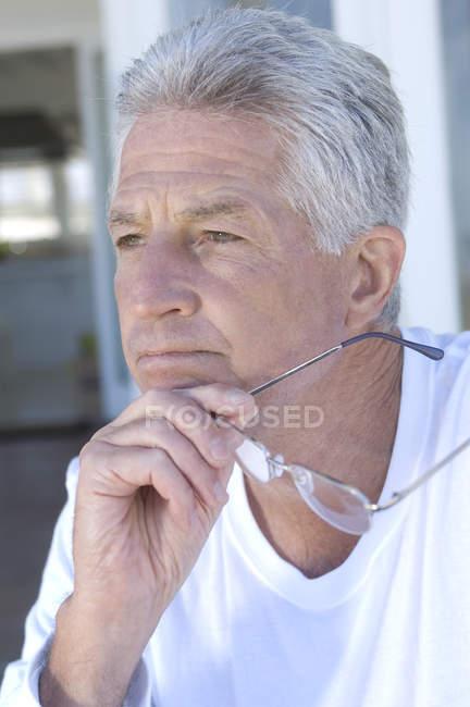 Portrait of thinking man holding eyeglasses — Stock Photo