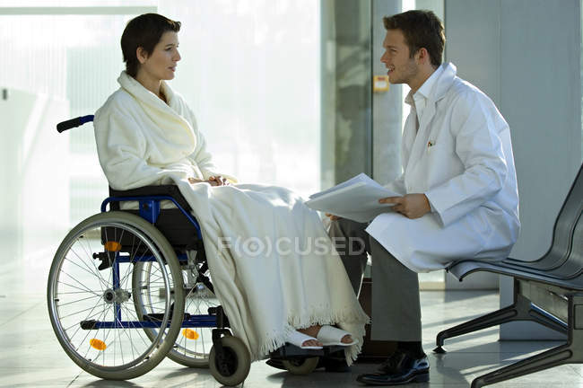Male doctor talking to female patient in wheelchair in hospital — Stock Photo