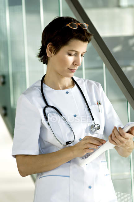 Female doctor reading medical records in hospital — Stock Photo