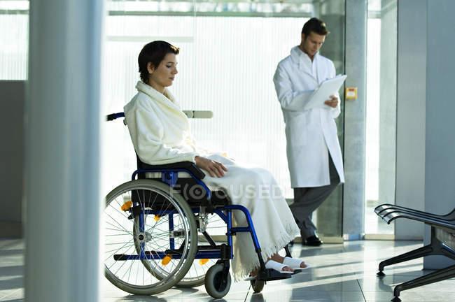 Пацієнтки, сидячи в інвалідному візку і чоловічого лікаря стоїть на тлі в лікарні — стокове фото