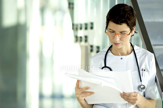 Female doctor reading medical records in clinic — Stock Photo