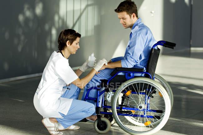 Medico femminile applicando medicina su mano paziente in ospedale — Foto stock