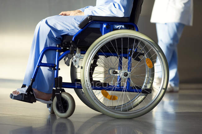 Low section view of patient sitting in wheelchair with doctor on background — Stock Photo
