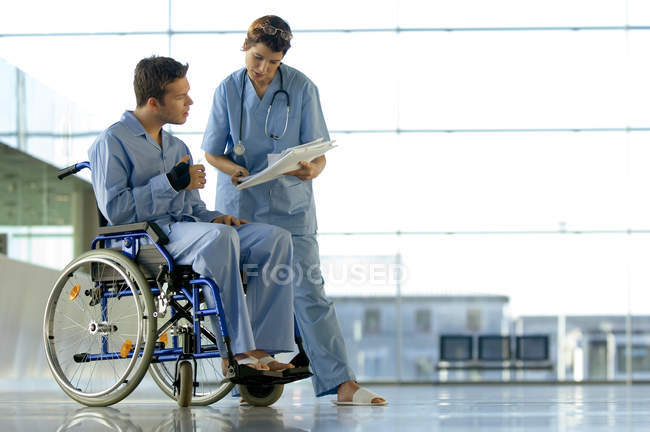 Female doctor showing medical record to patient in hospital — Stock Photo