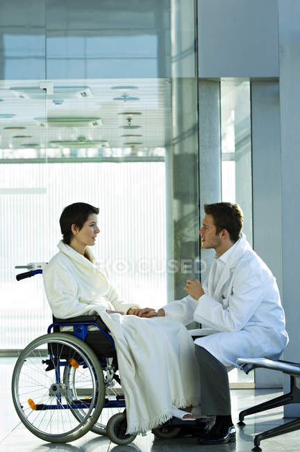 Male doctor consoling disabled female patient in hospital — Stock Photo