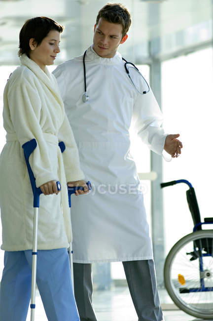 Male doctor assisting female patient in walking on crutches in hospital — Stock Photo