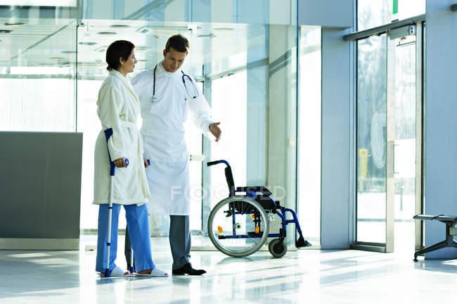Врач-мужчина помогает пациентке ходить на костылях в больнице — стоковое фото