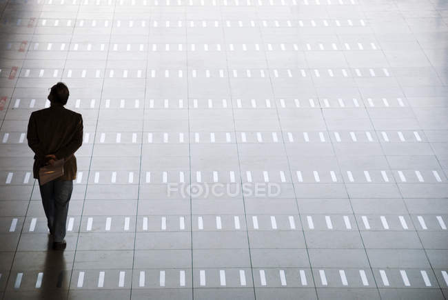 Rear view of silhouette of man walking at airport — Stock Photo