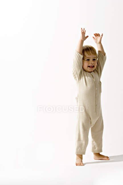 Baby boy standing with his arms raised and smiling — Stock Photo