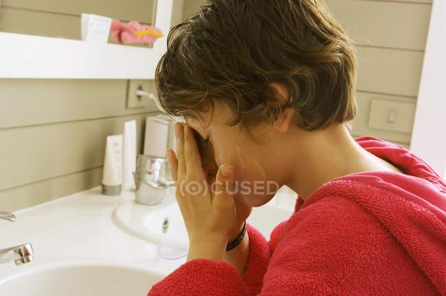 Little boy washing face in bathroom — Stock Photo