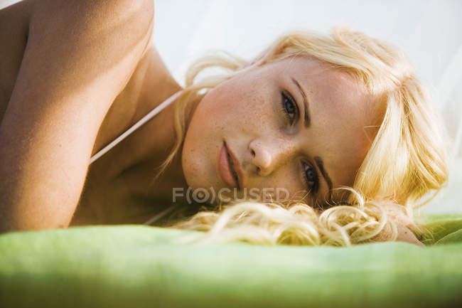 Young blond woman lying on blanket outdoors — Stock Photo
