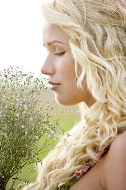 Портрет белокурый молодой женщины, держа букет цветов на открытом воздухе — стоковое фото