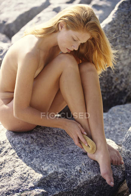 Naked young redheaded woman scrubbing foot with brush while sitting on rock - foto de stock