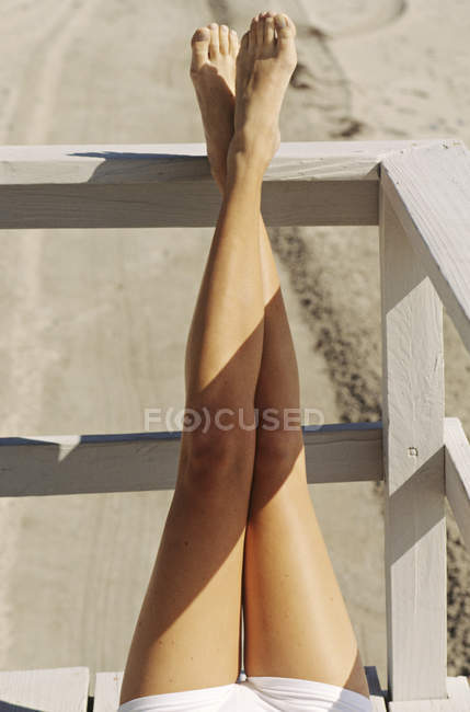 Female legs lying on wooden railing of balcony outdoors and sunbathing — Stock Photo