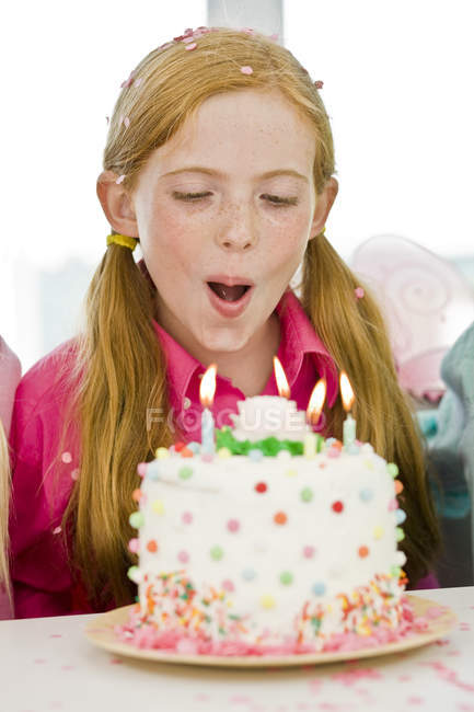 Close-up of ginger girl blowing out candles from birthday cake — Stock Photo