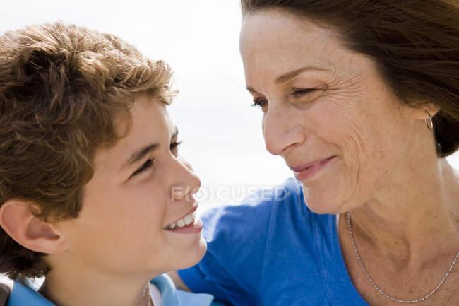 Frau und Enkel schauen einander an und lächeln — Stockfoto