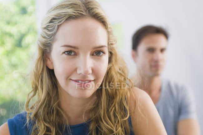 Ritratto di donna bionda sorridente che guarda la macchina fotografica con il marito sullo sfondo — Foto stock