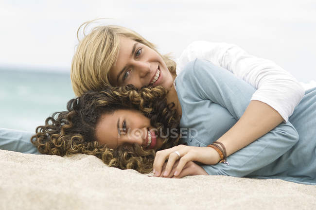 Portrait of teenage boy and girl relaxing on beach — Stockfoto