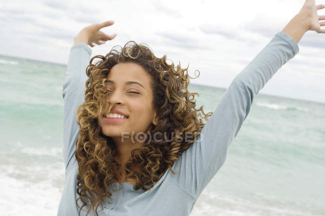 Close-up of happy teenage girl standing on beach with arms up — Stock Photo