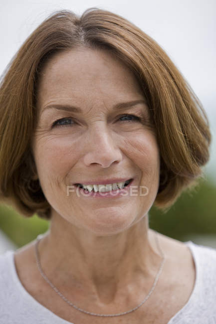 Portrait of mature woman smiling outdoors — Stock Photo