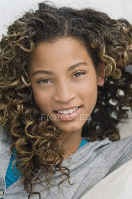 Portrait of latin american teenage girl lying on bed and smiling — Stock Photo