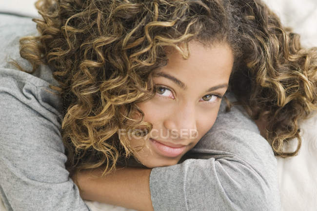 Portrait of latin american teenage girl lying on bed and smiling — Foto stock