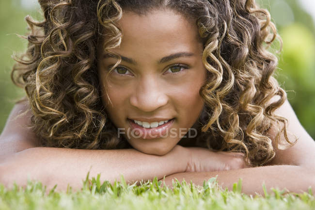 Portrait of latin american teenage girl lying on grass — Stock Photo