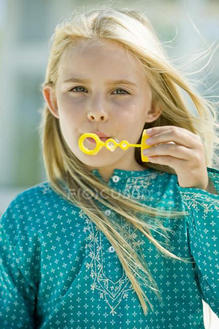 Retrato de menina soprando bolhas de sabão com varinha de bolha — Fotografia de Stock