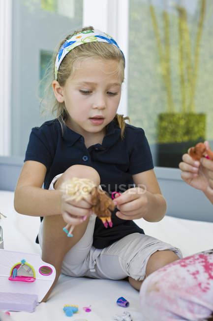 Petite fille jouer avec des jouets sur le lit à la maison — Photo de stock