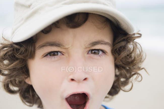 Ritratto di ragazzo in berretto che grida e guarda la macchina fotografica — Foto stock