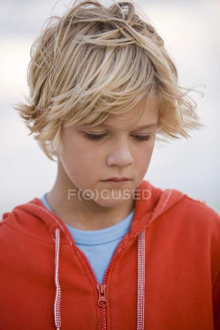 Nahaufnahme eines nachdenklichen blonden Jungen, der nach unten schaut — Stockfoto
