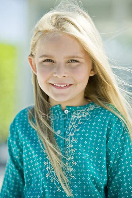 Retrato de una niña rubia sonriente mirando a la cámara sobre un fondo borroso - foto de stock