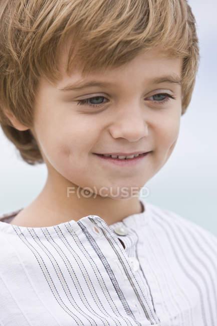 Крупный план маленького мальчика, улыбающегося на размытом фоне — стоковое фото