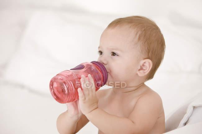 Малышка пьет воду из детской бутылочки — стоковое фото