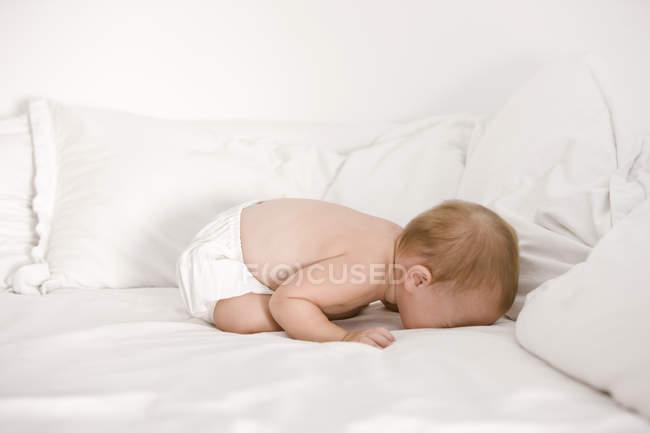 Niña sin camisa llorando en la cama - foto de stock