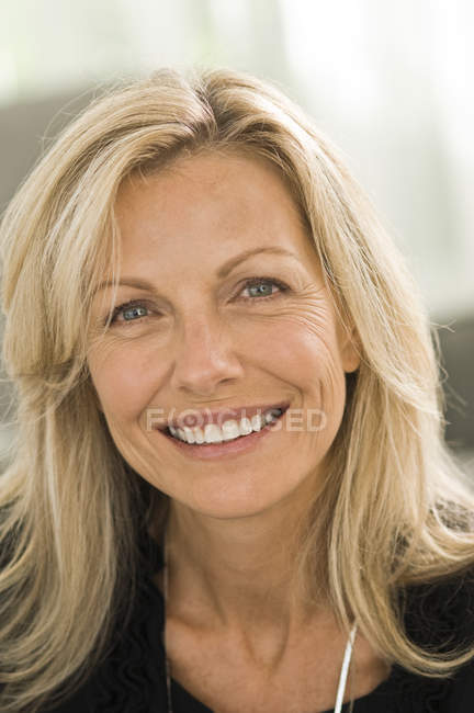 Portrait of blond mature woman smiling on blurred background — Stock Photo