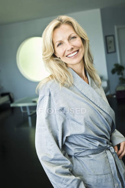 Portrait of mature woman in bathrobe smiling — Stock Photo
