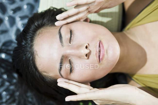 Close-up de mulher morena esfregando templos — Fotografia de Stock