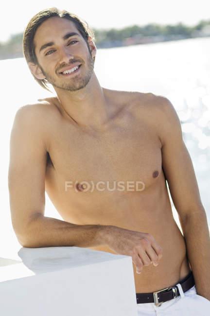 Retrato de un joven sin camisa relajándose en el lago - foto de stock