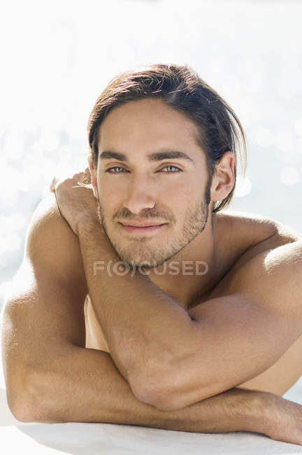 Portrait of sensual shirtless young man leaning on elbows at sea water — Stock Photo