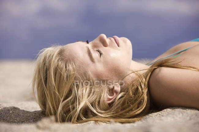 Close-up of blond young woman resting on sandy beach — Stock Photo