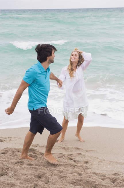 Couple joyeux marchant main dans la main sur la plage — Photo de stock