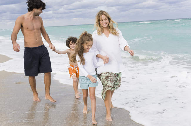 Happy family walking on sandy beach — Stock Photo